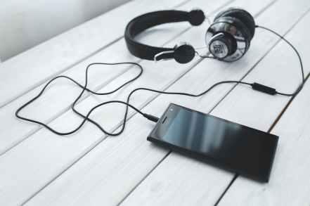 black smartphone and headphones on a desk